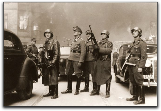 Jürgen Stroop directs the burning of the Ghetto (in center, in hat, not helmet, not obscured while Josef Blösche (on the far right) watches